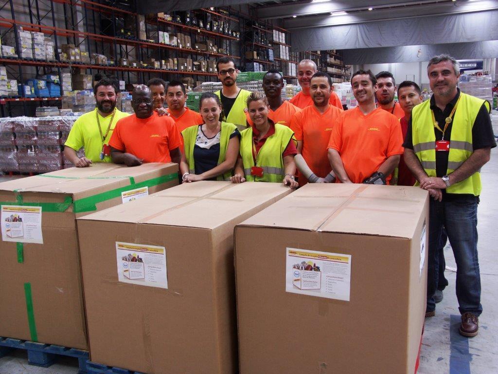 Empledados de DHL junto a las cajas de alimentos donados